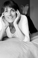 Woman lying forward on the bed smiling