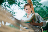 Woman lying in hammock writing diary