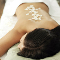 Woman lying on a massage table with rose petals on her back