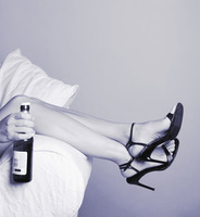 Woman lying on the couch holding a bottle of alcohol