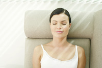 Woman lying on the couch with her eyes closed