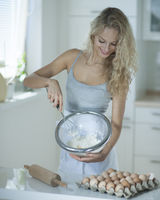 Woman mixing cookie batter in kitchen at counter