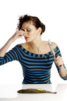 Woman pinching her nose while cutting a fish
