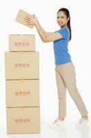 Woman placing a cardboard box on stack of boxes