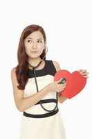 Woman placing stethoscope on a cut out heart