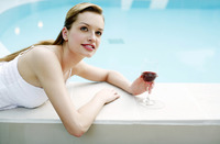 Woman relaxing by the pool side drinking red wine