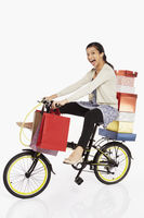 Woman riding a bicycle, carrying gift boxes and shopping bags
