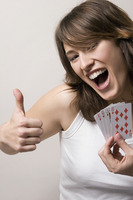 Woman showing thumbs up while holding playing cards