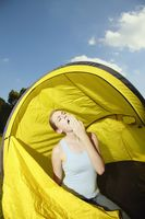 Woman sitting in the tent and yawning
