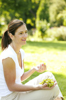 Woman sitting on the field eating green grapes