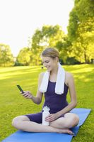 Woman sitting on yoga mat and text messaging on the phone
