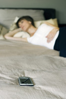Woman sleeping on the bed with pda by her side