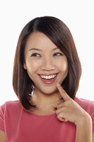 Woman smiling while holding up index finger