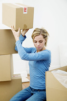 Woman stacking up sealed boxes