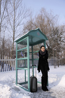 Woman standing near the telephone booth feeling cold