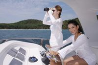 Woman steering yacht while another woman is looking through binoculars