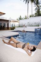 Woman sunbathing by the pool side, another woman jumping into the pool