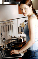 Woman using laptop while cooking in the kitchen