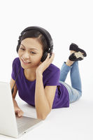 Woman using laptop while listening to music