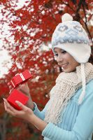 Woman wearing knit hat opening gift