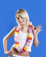Woman with flower leis smiling and waving