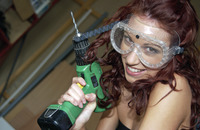 Woman with goggles holding a drill