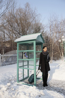 Woman with luggage standing at the telephone booth