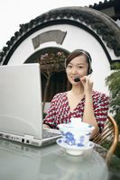 Woman with telephone headset using laptop