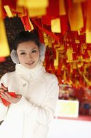 Woman writing wishes on red ribbon