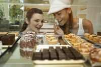 Women looking through display case at variety of cakes and tarts