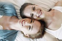 Women lying on bed with heads side by side