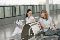 Women reading book and writing in organizer while waiting for train to arrive
