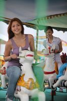 Women riding carousel horses at amusement park