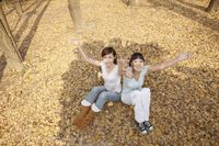 Women sitting and throwing dried leaves in the air