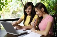 Women studying together using laptop