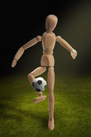 Wooden dummy model playing soccer