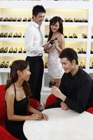 Young couple enjoying wine, another couple choosing wine in the background