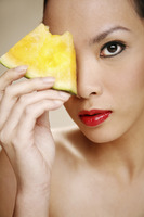 Young woman holding a slice of yellow water-melon