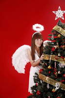 Young woman in angel costume standing beside christmas tree