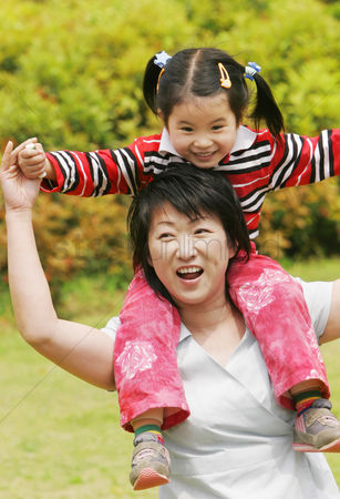 Park Outdoor : A woman giving her daughter a piggy back ride