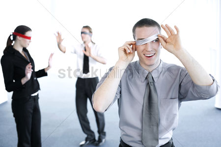 Business : Businessman cheating during a blindfolding game