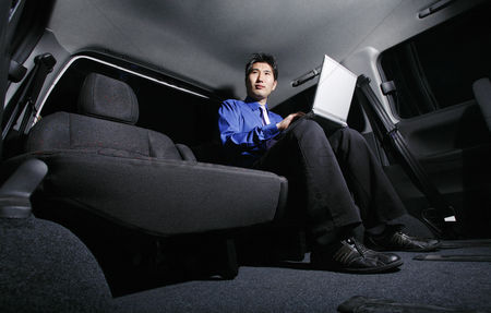 Interior : Businessman using laptop in the car