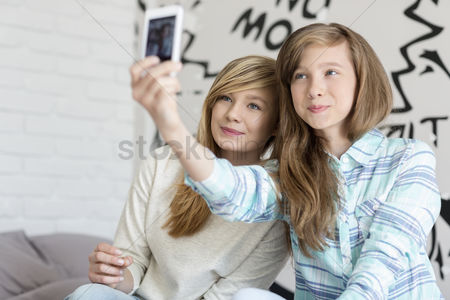 Selfie : Cute sisters taking photos with smart phone at home