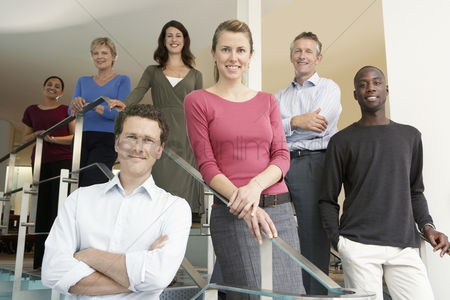 Interior : Group of office workers posing on office steps portrait