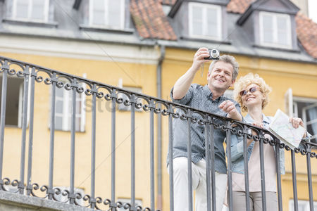 Selfie : Happy middle-aged couple taking selfie through digital camera against building