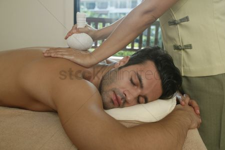 Spa : Man receiving a herbal pack massage from a massage therapist