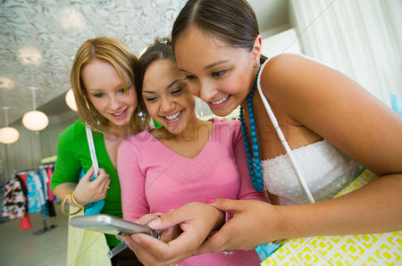 Girl : Three girls looking at cell phone picture