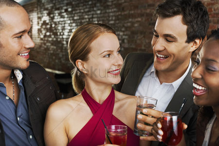 Party : Two couples laughing holding drinks in bar