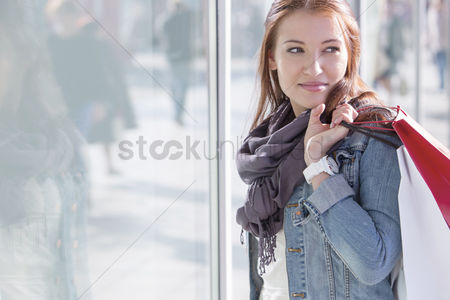 Shopping : Woman carrying shopping bags while standing by store