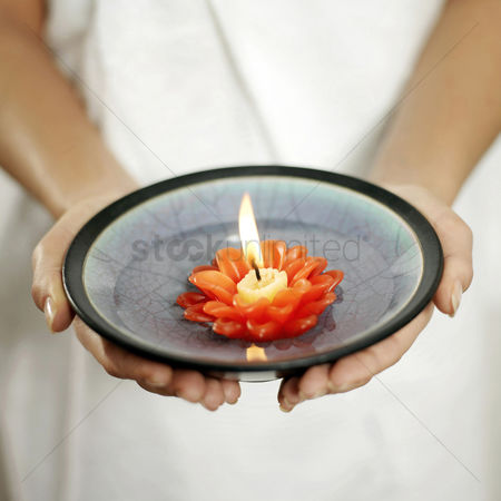 Water : Woman holding a bowl of water with lit candle floating on it
